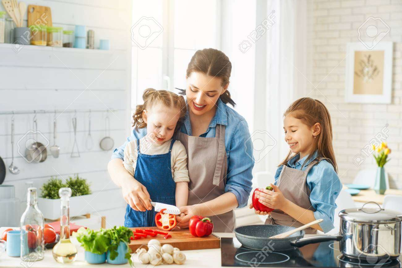 123150909 healthy food at home happy family in the kitchen mother and children daughters are preparing vegetab