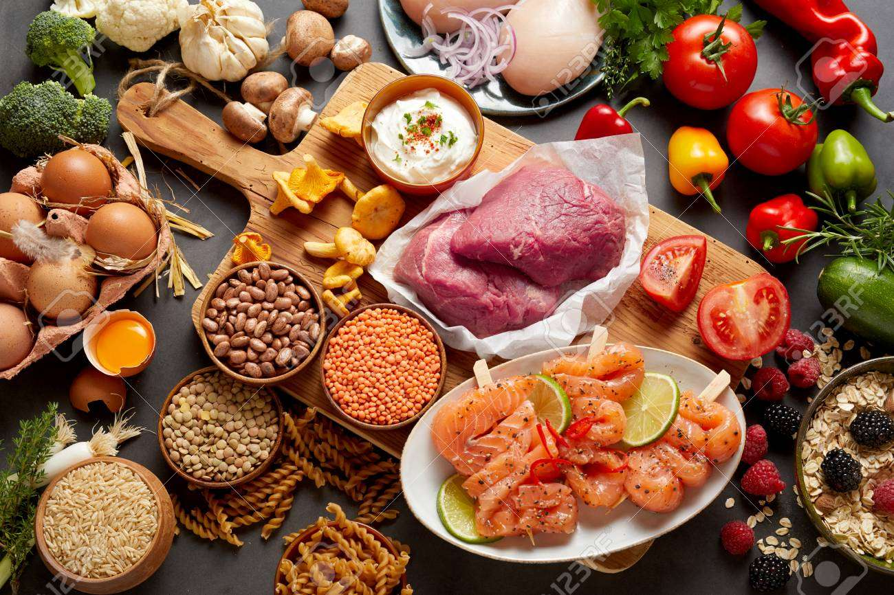 85569533 a rustic assortment of paleo foods including eggs legumes vegetables fish meat muesli and pasta on a